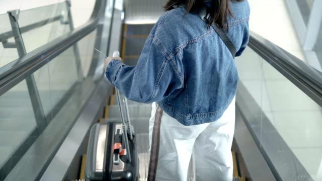 using escalator in airport terminal. - donna valigia solitudine video stock e b–roll