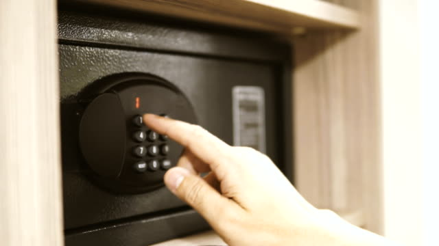 Using Hotel Code Safe. The man opens the code safe and puts in his valuable papers and documents, cinematic dof video