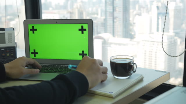 Using Labtop Green Screen With High Rise Office Background Stock