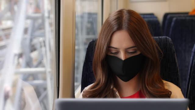 med hjälp av laptop bär en ansiktsmask, tågresa. - affärsresa bildbanksvideor och videomaterial från bakom kulisserna