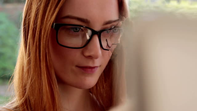 Using laptop, young woman wearing glasses. video