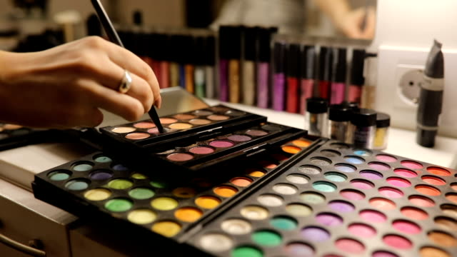 Using make up Make up artist workplace, multi-colored make up eqipment in make up studio, woman using make up. eyeshadow stock videos & royalty-free footage