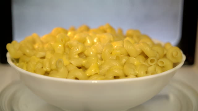Using microwave to heat up food. Warming up cooked macaroni and cheese Using microwave to heat up food. Warming up cooked macaroni and cheese in microwave. Mac and cheese bowl spins inside oven. macaroni stock videos & royalty-free footage