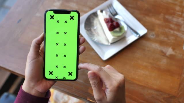 stockvideo's en b-roll-footage met met behulp van mobiele telefoon met groen scherm in restaurant - breakfast table