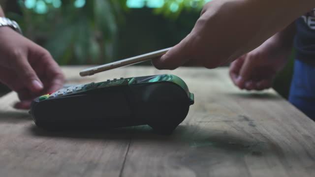 vídeos de stock, filmes e b-roll de usando a tecnologia nfc para pagar com o celular, pagamento sem contacto - pagando