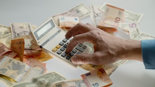 vídeos y material grabado en eventos de stock de usar una calculadora antigua para contar dinero - accesorio financiero