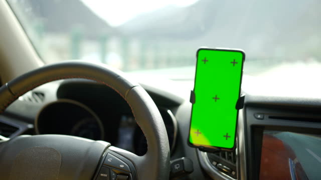 vídeos de stock e filmes b-roll de using on smart phone with green screen while driving - bluetooth