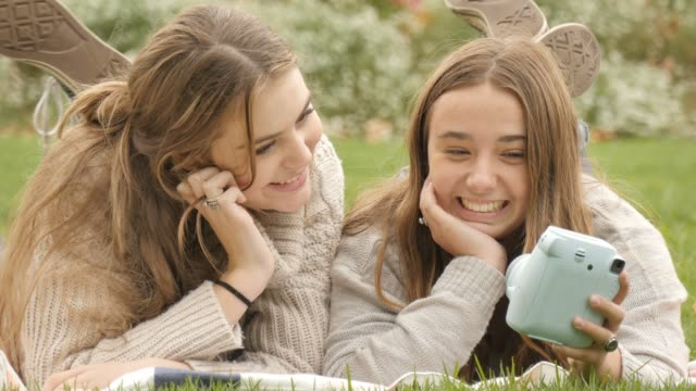 stockvideo's en b-roll-footage met met behulp van retro polaroid camera om selfie foto's te maken twee tiener meisjes met plezier - polaroid