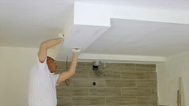 utilizzo di carta di sabbia sulla parete per la lucidatura - carta vetrata video stock e b–roll