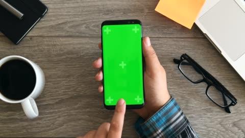 vídeos de stock, filmes e b-roll de usando o telefone inteligente exibindo chromakey - smartphone