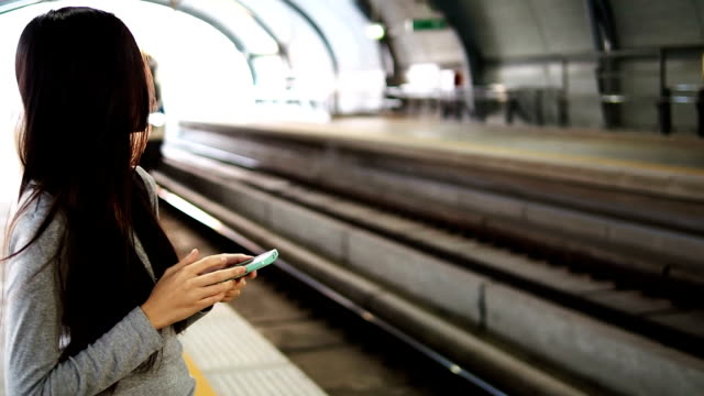 using smart phone while waiting for a train video
