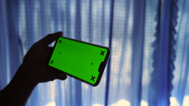 Using Smart Phone with Green Screen in Bed Room with Sunlight Through Curtains