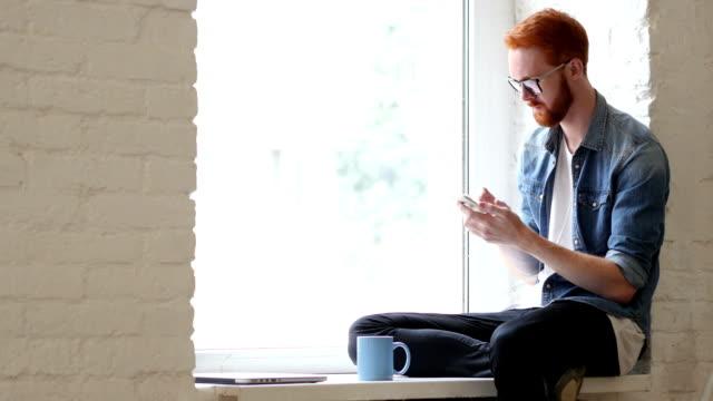 Using Smartphone, Browsing Online by Man Sitting in Window video