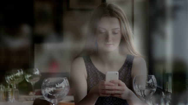 Using smartphone, young woman in a restaurant, view through a window. video
