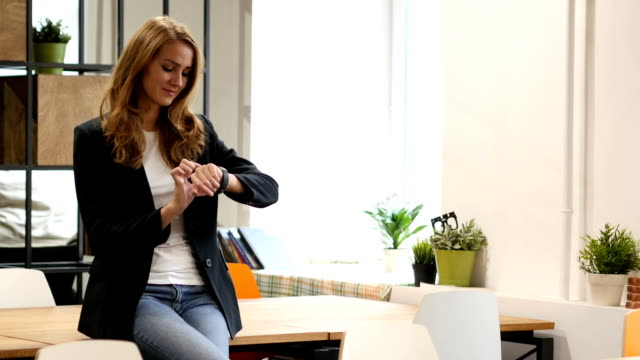 Using Smartwatch, Business woman Sitting on Desk in Office video
