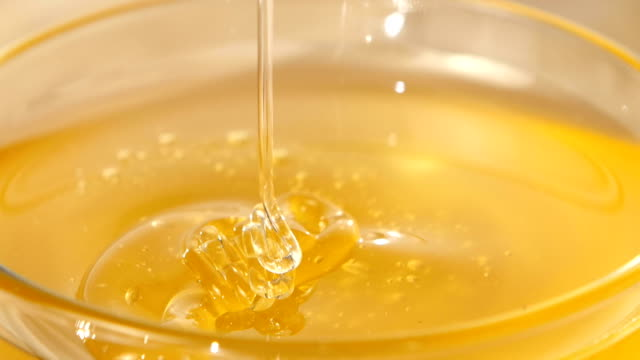 Using spoon for honey in bowl, pick it up, close up video