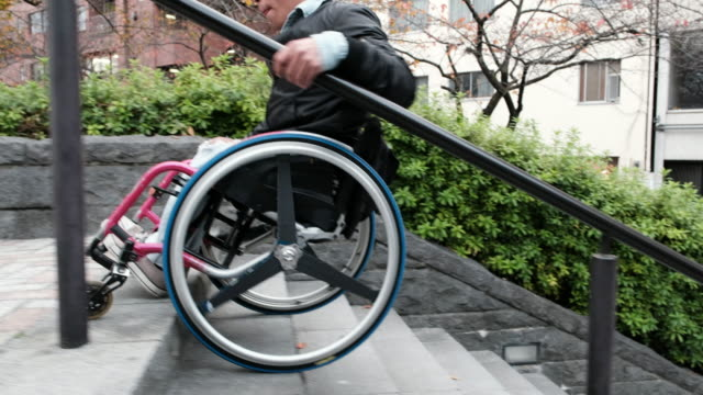Using Stairs in a Wheelchair A Japanese man in a wheelchair goes down sidewalk steps in Tokyo, Japan. conquering adversity stock videos & royalty-free footage