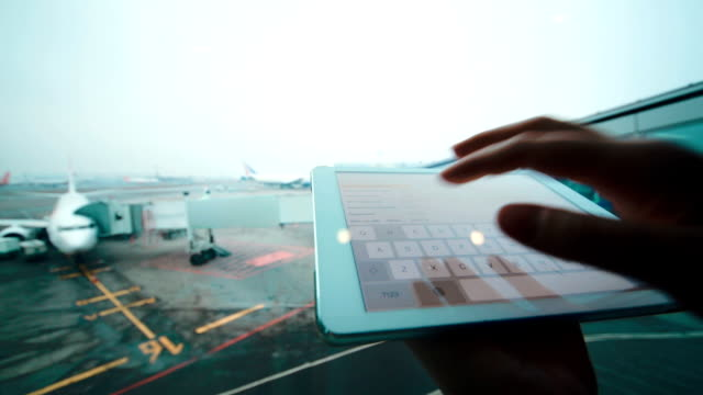 Using tablet computer by the window at airport video