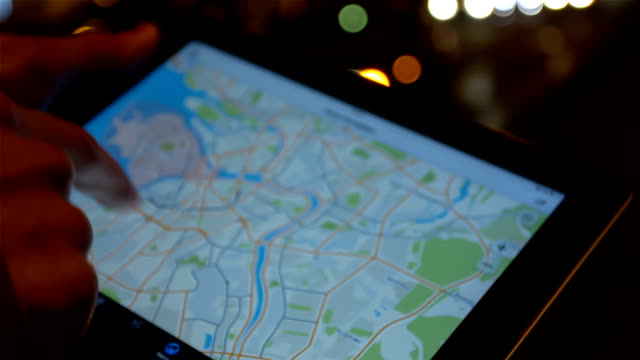 Using Tablet Pc With a Map Man uses tablet with a map (scrolling, touching) on the night street in the center of the city in the background. goal post stock videos & royalty-free footage