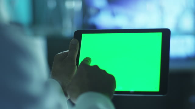 använda tablet med grön skärm i liggande läge. vetenskaplig miljö. - videor med medicinsk undersökning bildbanksvideor och videomaterial från bakom kulisserna