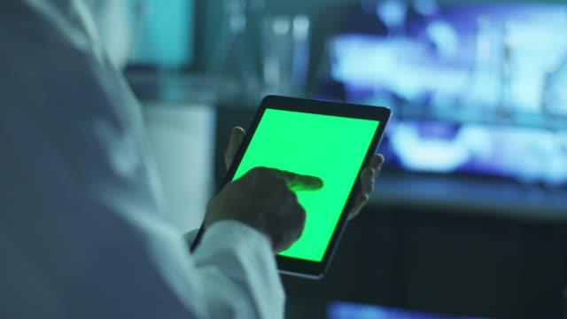 använda tablet med grön skärm i porträttläge. vetenskaplig miljö. - videor med medicinsk undersökning bildbanksvideor och videomaterial från bakom kulisserna