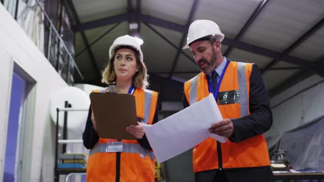 using the greatest tool at their disposal...teamwork - ispettore della qualità video stock e b–roll