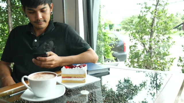Using using smartphone at coffee cafe with cake video