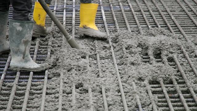 uso del vibratore per spingere il calcestruzzo attraverso la griglia metallica - cemento video stock e b–roll