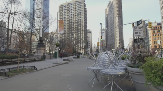 di solito affollata flatiron public plaza, all'angolo tra la 5th avenue e east 23rd street, ora deserta a causa dell'epidemia di coronavirus covid-19. new yrk city, stati uniti - inquadratura fissa video stock e b–roll