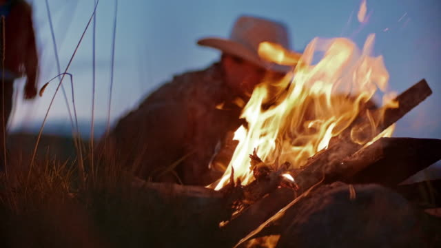 Utah Rancher Family by the bonfire Cowboy family sitting around bonfire  in the open field outside Salt Lake City, Utah. Playing music on guitars, roasting snacks on fire, enjoying the early evening by the flame. wild west stock videos & royalty-free footage