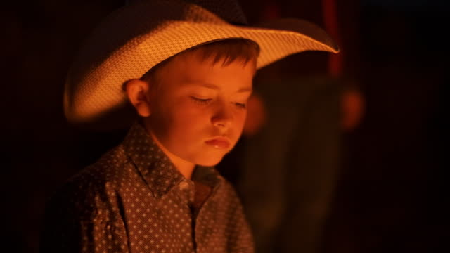 Utah Rancher Family by the bonfire Cowboy family sitting around bonfire  in the open field outside Salt Lake City, Utah. Playing music on guitars, roasting snacks on fire, enjoying the early evening by the flame. cowgirl stock videos & royalty-free footage