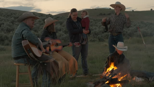 Utah Rancher Family by the bonfire Cowboy family sitting around bonfire  in the open field outside Salt Lake City, Utah. Playing music on guitars, enjoying the early evening by the flame. cowgirl stock videos & royalty-free footage