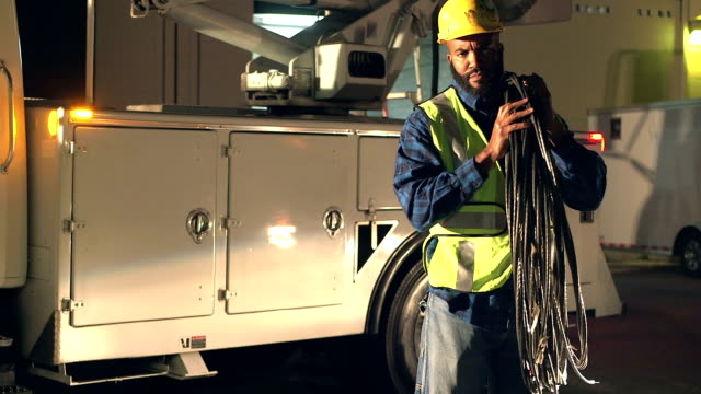 Utility worker in safety vest lifting cables, by truck video