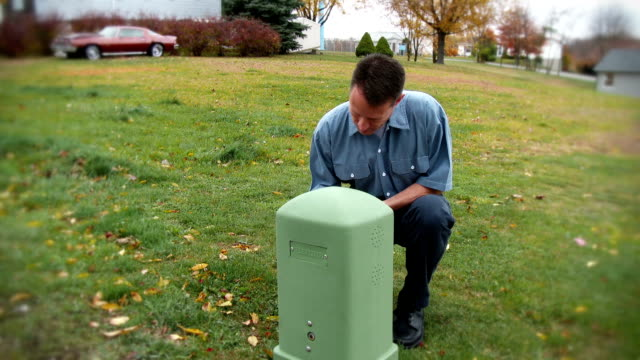Utility Worker A utility worker inspects an exterior utility outlet. cable tv stock videos & royalty-free footage
