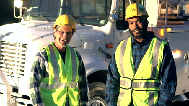 Utility workers in safety vests and hardhats by truck video