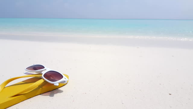 v02369 Maldives beautiful beach background white sandy tropical paradise island with blue sky sea water ocean 4k yellow flip flops sunglasses Maldives beautiful beach background white sandy tropical paradise island with blue sky sea water ocean 4k yellow flip flops sunglasses indian ocean islands stock videos & royalty-free footage
