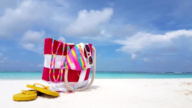 v02391 Maldives beautiful beach background white sandy tropical paradise island with blue sky sea water ocean 4k bag bikini flip flops Maldives beautiful beach background white sandy tropical paradise island with blue sky sea water ocean 4k bag bikini flip flops indian ocean islands stock videos & royalty-free footage