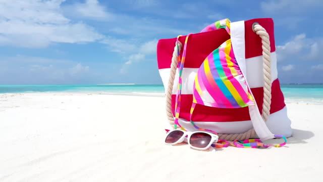v02395 Maldives beautiful beach background white sandy tropical paradise island with blue sky sea water ocean 4k bag bikini sunglasses Maldives beautiful beach background white sandy tropical paradise island with blue sky sea water ocean 4k bag bikini sunglasses indian ocean islands stock videos & royalty-free footage