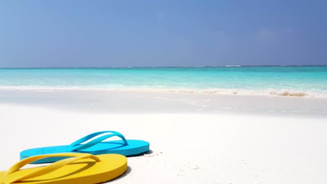 v02553 Maldives beautiful beach background white sandy tropical paradise island with blue sky sea water ocean 4k flip flops video