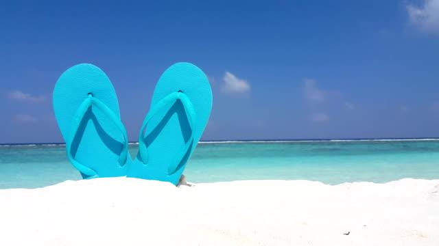 v02555 Maldives beautiful beach background white sandy tropical paradise island with blue sky sea water ocean 4k flip flops video