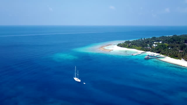 v03007 Aerial flying drone view of Maldives white sandy beach on sunny tropical paradise island with aqua blue sky sea water ocean 4k boat sailing video