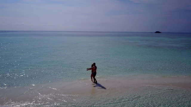 v03959 Aerial flying drone view of Maldives white sandy beach 2 people young couple man woman romantic love on sunny tropical paradise island with aqua blue sky sea water ocean 4k video