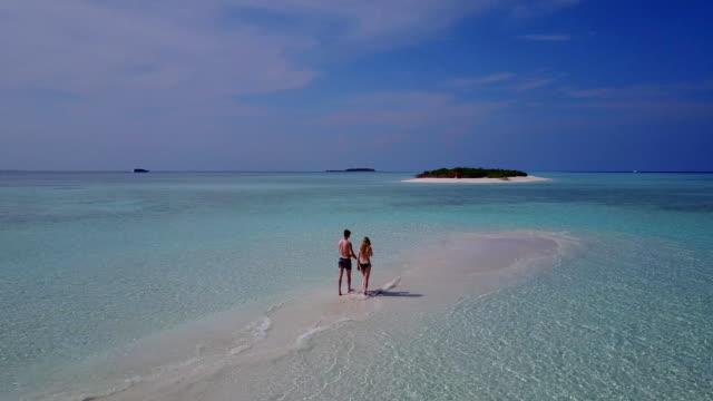 v04014 flygande drönare flygfoto över maldiverna vit sandstrand 2 personer ungt par man kvinna romantisk kärlek på solig tropisk paradisö med aqua blå himmel sjö vatten hav 4k - idyllisk bildbanksvideor och videomaterial från bakom kulisserna