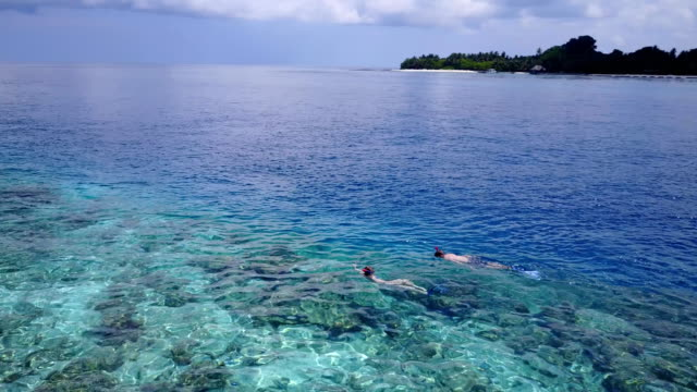 v04060 Aerial flying drone view of Maldives white sandy beach 2 people young couple man woman snorkeling swimming diving on sunny tropical paradise island with aqua blue sky sea water ocean 4k video