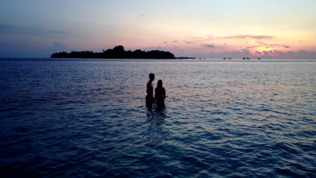 v04157 Aerial flying drone view of Maldives white sandy beach 2 people young couple man woman romantic love sunset sunrise on sunny tropical paradise island with aqua blue sky sea water ocean 4k video