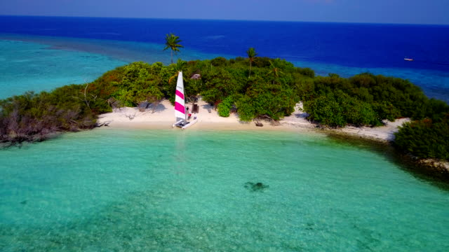 v04338 Aerial flying drone view of Maldives white sandy beach on sunny tropical paradise island with aqua blue sky sea water ocean 4k video