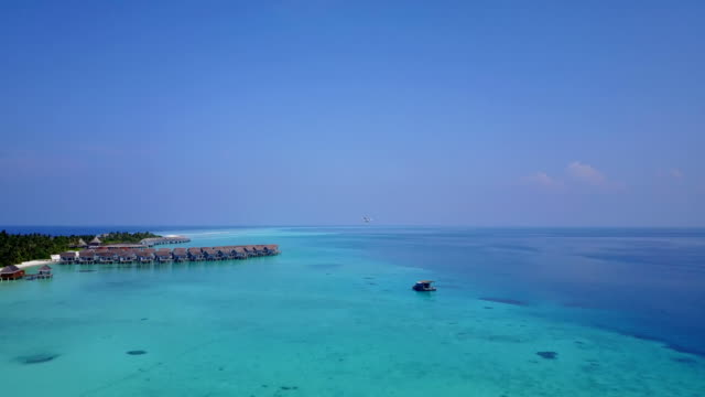 v04499 Aerial flying drone view of Maldives white sandy beach on sunny tropical paradise island with aqua blue sky sea water ocean 4k video