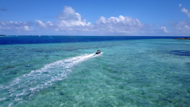 v06201 Aerial flying drone view of Maldives white sandy beach jetski riding sunny tropical paradise island with aqua blue sky sea water ocean 4k