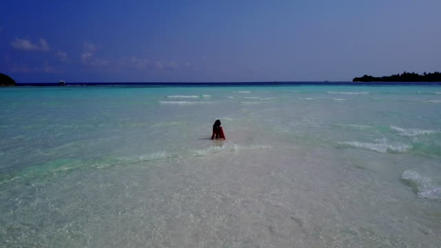 v06276 Aerial flying drone view of Maldives white sandy beach 1 person young beautiful lady on sandbar on sunny tropical paradise island with aqua blue sky sea water ocean 4k video