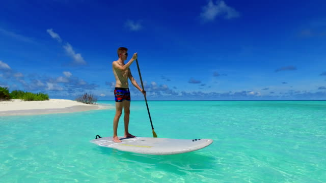 v07365 Maldives white sandy beach 2 people young couple man woman paddleboard rowing on sunny tropical paradise island with aqua blue sky sea water ocean 4k video